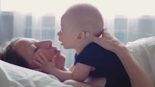 A young and happy mother and her small son. Resting together at bed. Maternity concept. Parenthood. Motherhood Beautiful Happy Family Footage.