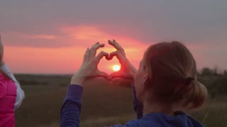 A young girl making heart symbol with her hands at sunset