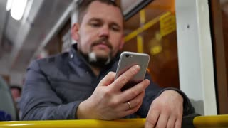 A young man using a smartphone on the bus.