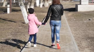 A young mother and a beautiful daughter are walking around the city park