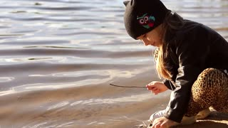 Adorable little girl wearing a black jacket playing at a river shore throwing tree branches into the water on a hot sunny spring day.