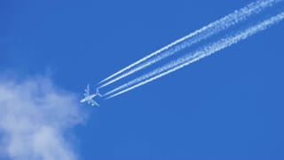 Airplane contrail against clear blue sky. Trace of the plane in the sky.