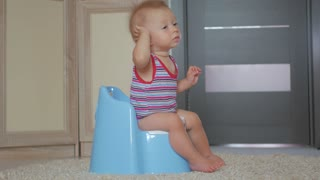 Baby boy on the potty at home.