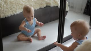 Baby boy play with own reflection in mirror.