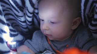 baby boy playing with flashlights lying in bed