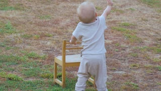 Baby boy walking with help of a chair outdoor.