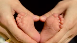 Baby feet in mother hands. Tiny Newborn Baby's feet on female Heart Shaped hands closeup. Mom and her Child. Happy Family concept. Beautiful conceptual video of Maternity.