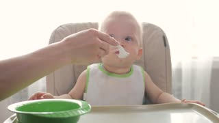 Baby sits at a children's little table. Mum feeds the child with porridge. Mother gives baby food from a spoon.