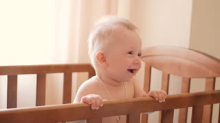Baby standing in bed at home. Portrait of baby boyl stand in cot. Baby eyes looking for mother.