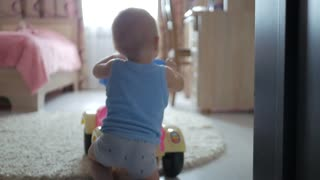 Baby with learning walker in the home.