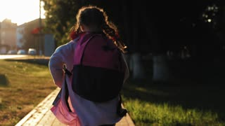 Back to school. Child girl with backpack going to school with fun. Happy little girl with schoolbag on a street. The concept of school, study, education, childhood. Pretty schoolgirl running in park.