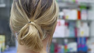 Back view of pharmacist chemist woman standing in pharmacy drugstore and checking a medication.