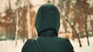 Back view portrait of young girl walks in winter park. Snow covered park wearing winter clothes, layered sweaters and mittens holding park hood.