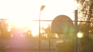 Basketball In The Sunset. Playing basketball at the sunset. The game of basketball on outdoor playground.