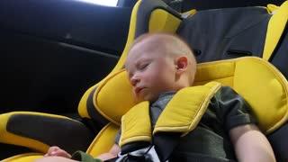 beautiful baby boy sleeping in car seat.