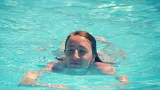 Beautiful cute woman enjoys water in swimming pool.