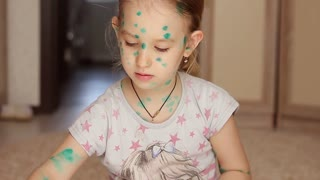 Beautiful girl being ill with chickenpox, draws a picture at home. Play without thinking about the disease concept. The face in the green points. Children's drawing.