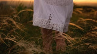 Beautiful girl wearing white dress running through beautiful field at sunset. Young woman jogging at the meadow and enjoying freedom. Summer leisure at nature concept.