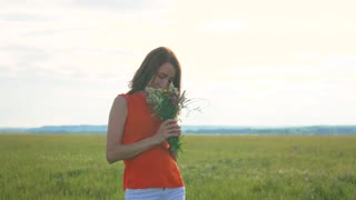 Beautiful girl with field flowers standing in a meadow.