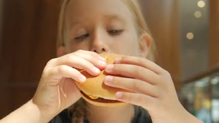 Beautiful happy hungry baby girl eating hamburger. Fast food concept. Tasty unhealthy burger sandwich in hands.