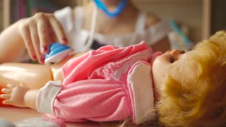 Beautiful little girl playing doctors with doll at home.