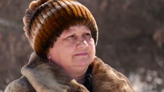Beautiful older woman on a walk in winter forest