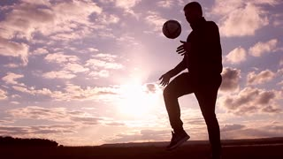 Beautiful sunset and silhouettes of men playing football, kick a soccer ball, goalkeeper catches ball