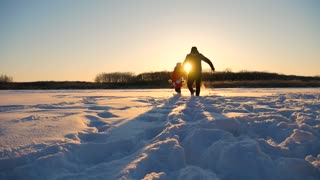 Beautiful sunset, father and daughter running to the sunset, winter.