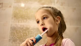Beautiful young girl brushes teeth by electric brush, smiling, drops out milk teeth, concept of health.
