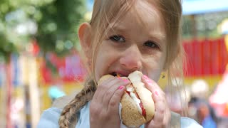 Beautiful young girl eating a hot dog in a park.