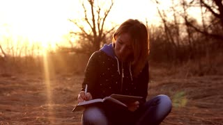 Beautiful young girl, sitting on a fallen autumn leaves in a park, reading tablet computer to take notes in a notebook, sunset light. Concept girl freelancer, working in a spring park.