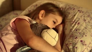Beautiful young girl sleeping in bed with teddy bear.