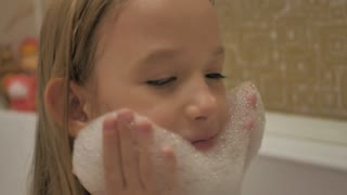 Beautiful young girl taking a bath. Kid is washing herself and blowing to the foam. Pieces of foam flying around.