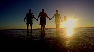 Big family jumping on the beach at sunset. Concept of friendly family.