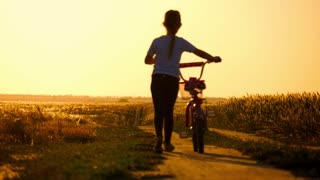 Biker-girl at the sunset on the meadow. Child enjoying freedom on bike on wheat field at sunset. Girl on a bike in the countryside in sunset time.