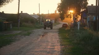Blue tractor rides down the street village at sunset, Russia.