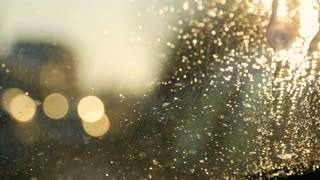 Blurred lights of city with sunset, vintage tone. Rain drops texture on window glass sunset light abstract blurred cityscape skyline bokeh background. Soft focus.