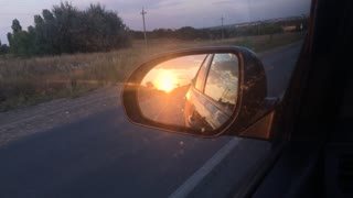 Car rides on the road, a view of the side rearview mirror, reflection in the mirror. View of the bay from the car. Close-up.