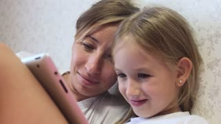 Charming little girl and her beautiful young mom are using a digital tablet and smiling while sitting on sofa at home