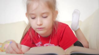 Charming little girl reading book on sofa