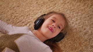 Cheerful young girl listening music in headphones lying on floor at home