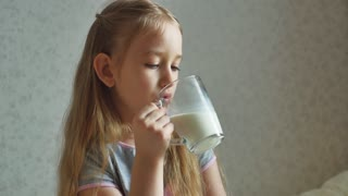 Child drinking milk at the home.