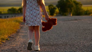 Child hand holding teddy bear at a sunset time.