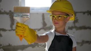 childhood, construction, architecture, building and people concept - smiling little girl in protective yellow helmet and safety glasses with brush for paint