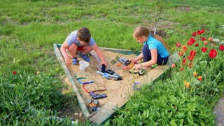 Children play in the sand in the backyard of the house.