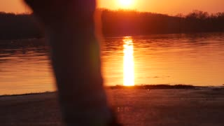 Children play on a lake at sunset. Silhouettes of a little girl and boy spend time together next, run and play. The concept of children's friendship, slow-motion footage.