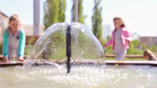 Children playing with water in park fountain. Hot summer. Happy children have fun playing in water fountains.
