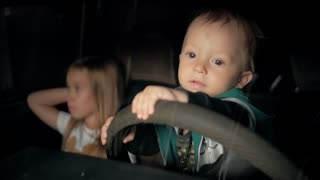 Children pretend driving car sitting on front vehicle seats