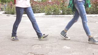 Close-up, legs of teenagers walking in the park. The concept of the holiday, people go one after another.