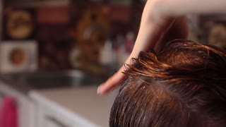 Close up of a hairdresser cutting hair. Hands of professional hair stylist.